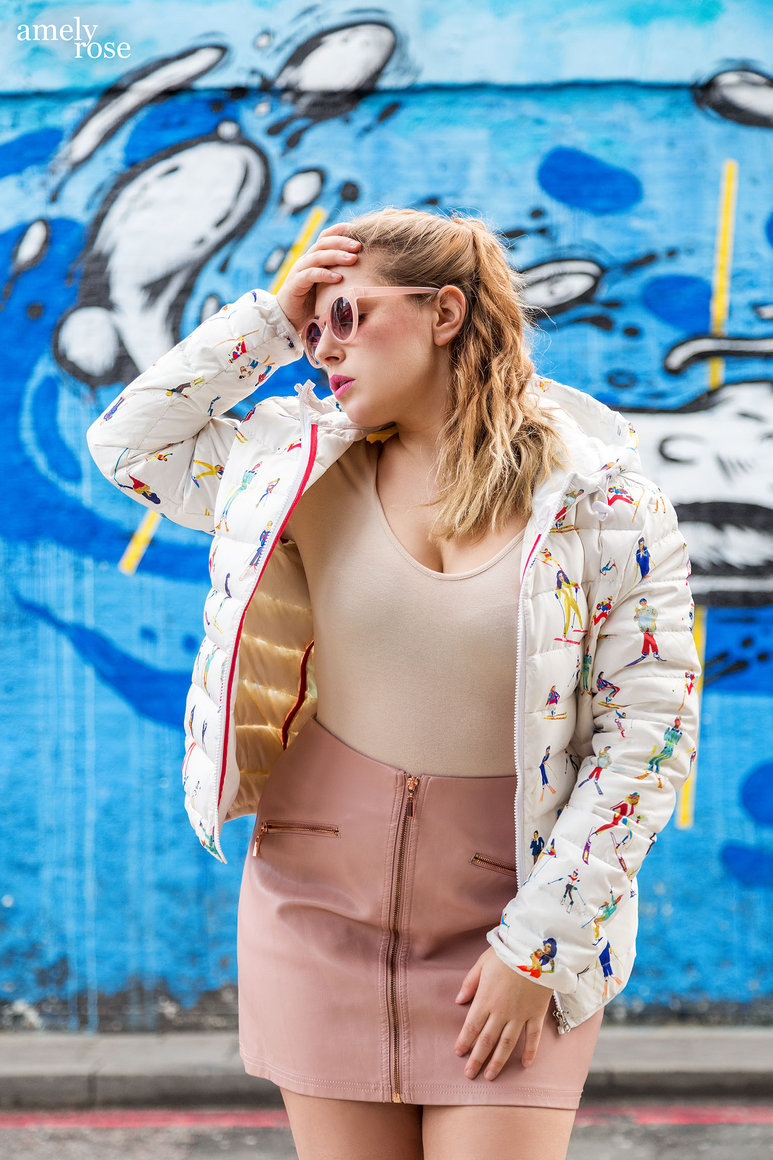 Amely Rose in einer Designer Winterjacke vor einem blauen Graffiti in London.