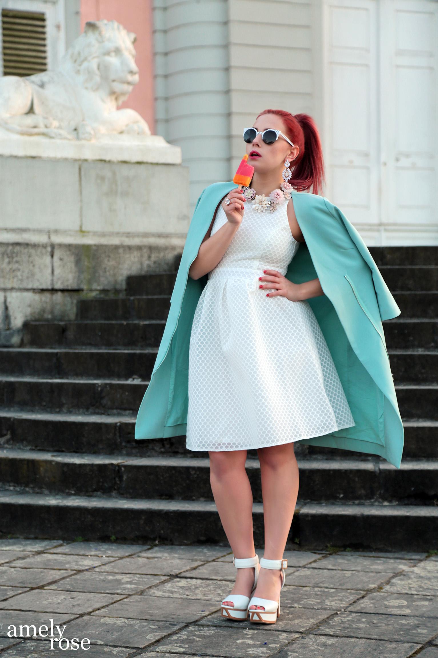 amely rose in einem sommeroutfit mit einem blauen mantel