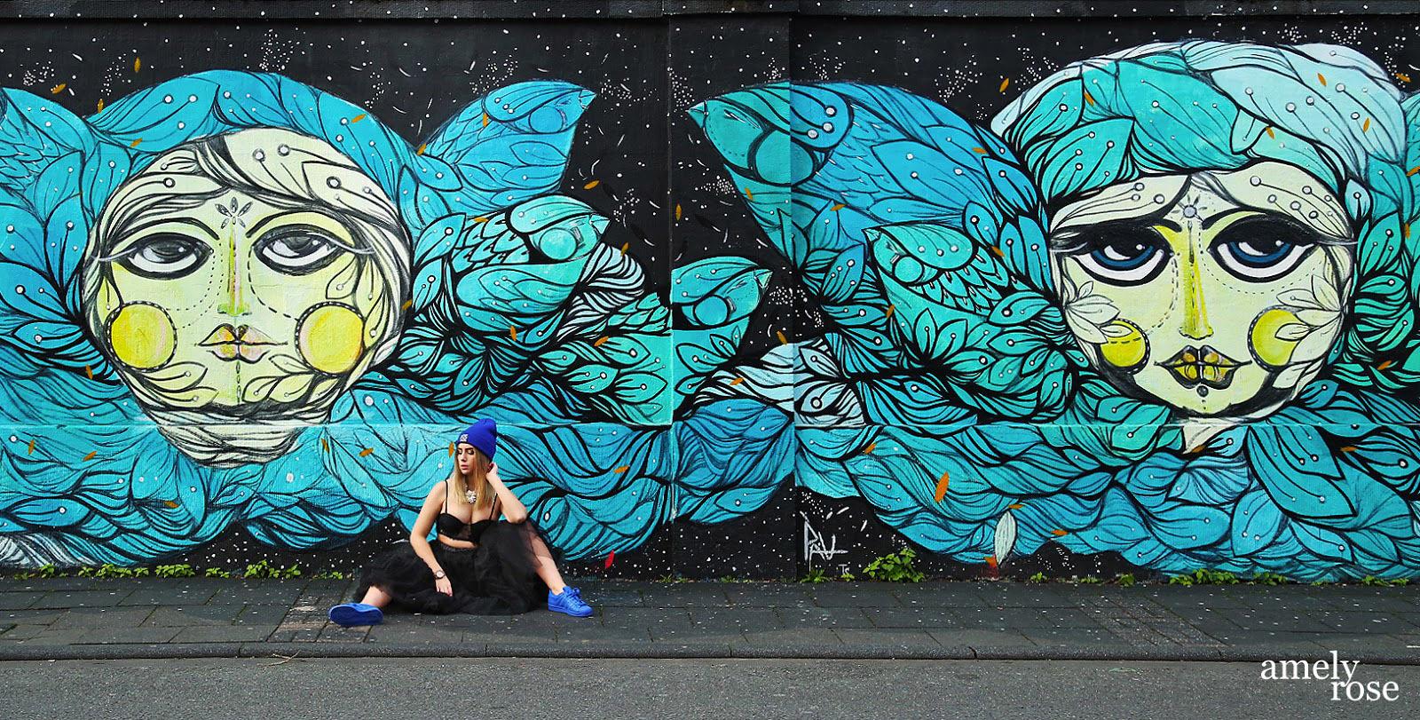 amely rose vor einem tollen blauen graffiti in köln ehrenfeld.wer streetart mag und fashion wird diesen post lieben. all black everything und eine tolle fake fur jacke. ein coat mit blauen franzeln.
