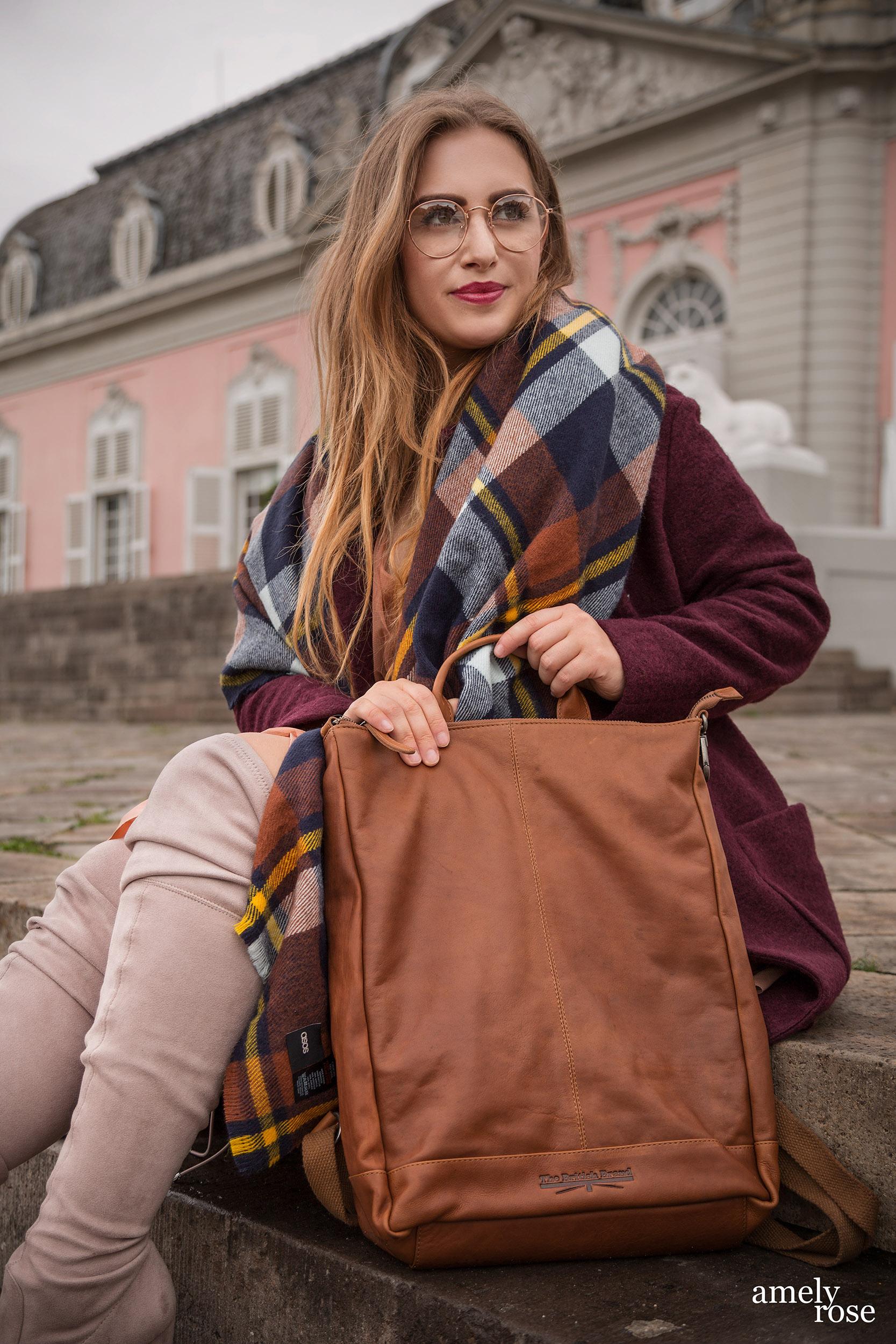 Amely Rose zählt zu den erfolgreisten deutschen fashionblogger. Sie zeigt einen herbstlook mit erdigentönen einem wollmantel von H&M, sowie einem Zara Kleid, Overkneeboots und einem oversize Schal. Dazu ein schöner lederrucksack kombiniert.