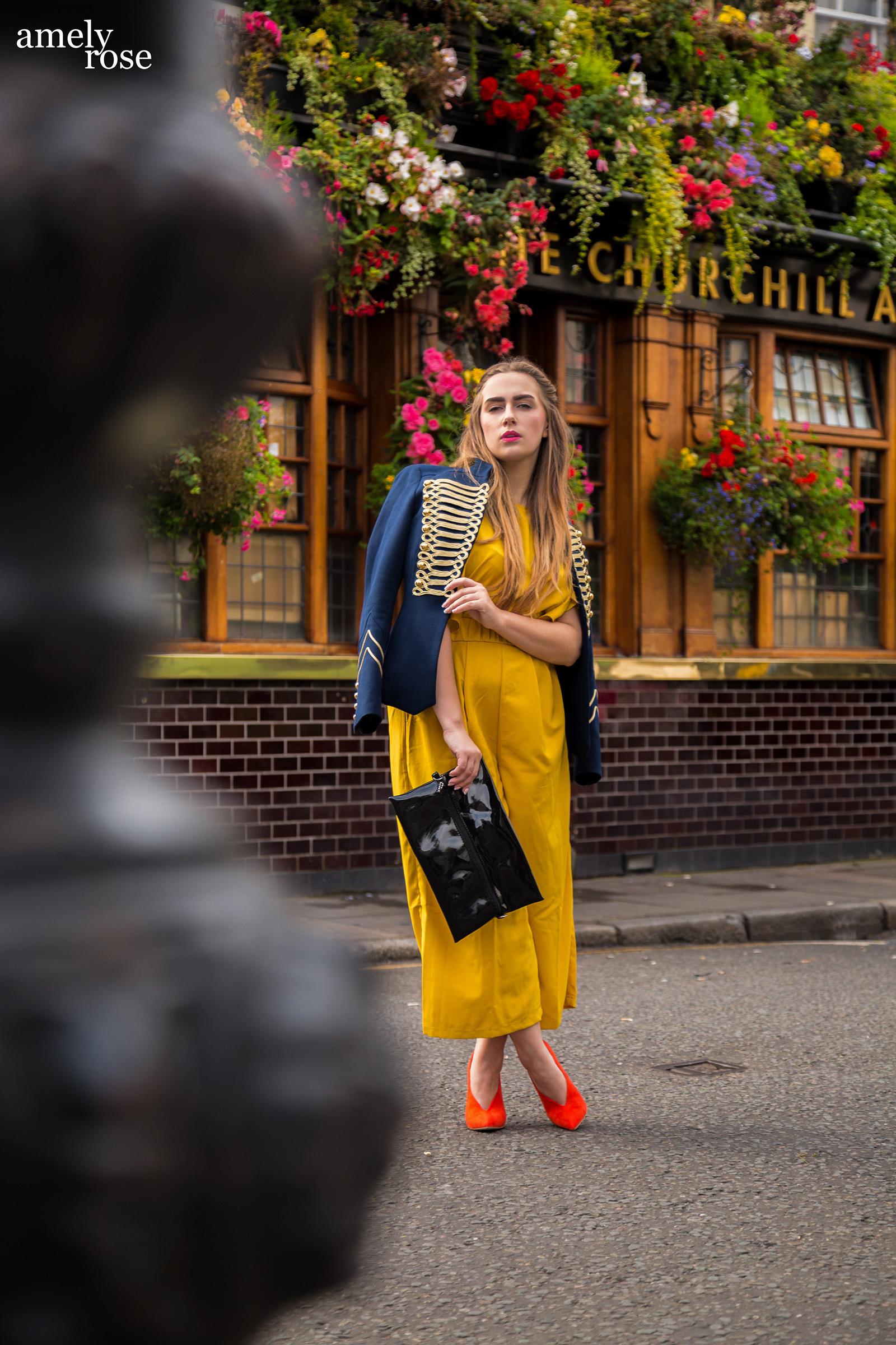 Amely Rose zur Fashionweek in London vor demlondoner Hotspot Pub Churchill arms im gelben Enteiler, Zara Jacke und orangen Pumps.