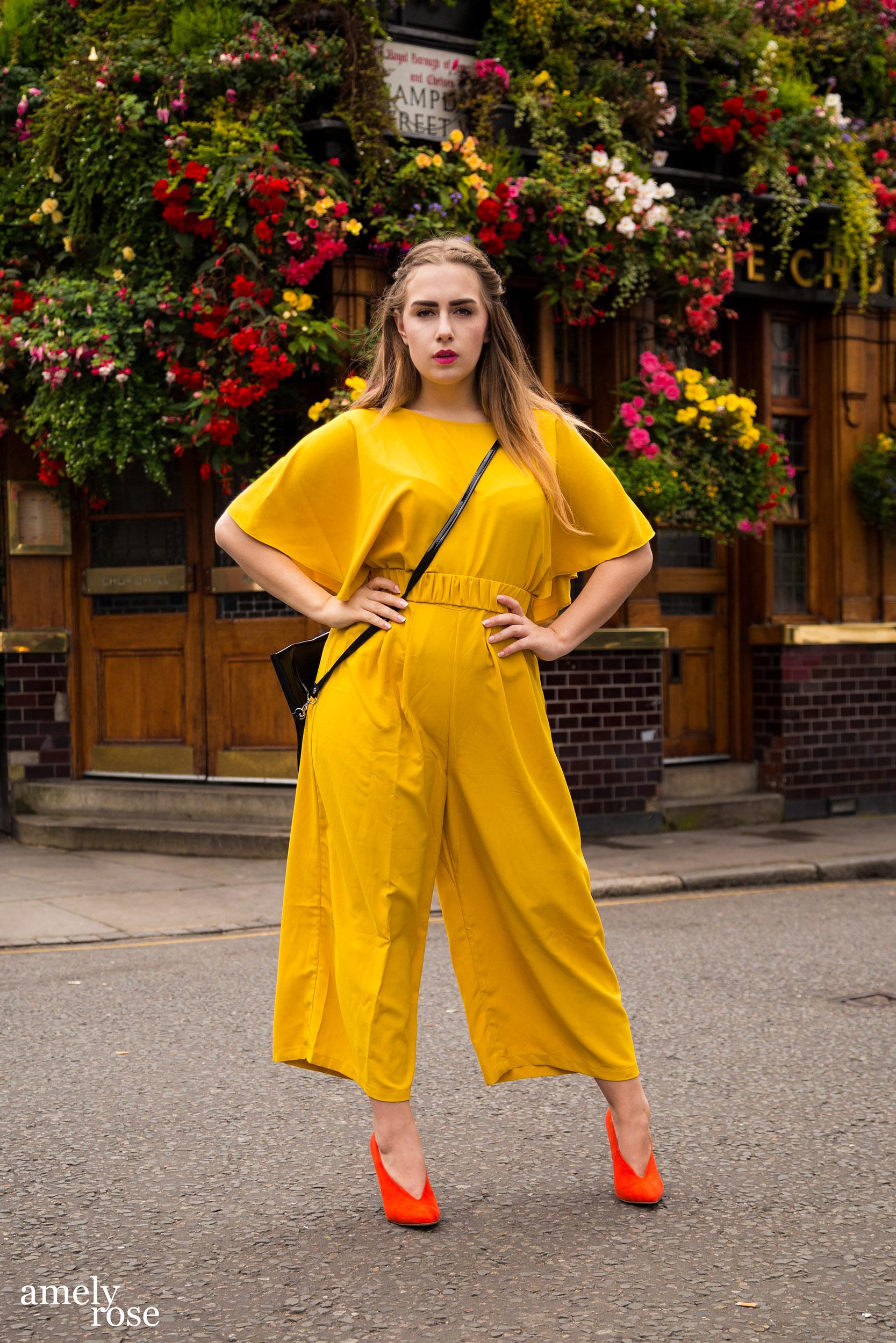 amely rose, deutsche Fashionbloggerin in London während der London Fashionweek LFW in einem gelben Einteiler vor dem Londoner Hotspot Pub Chruchillarm.